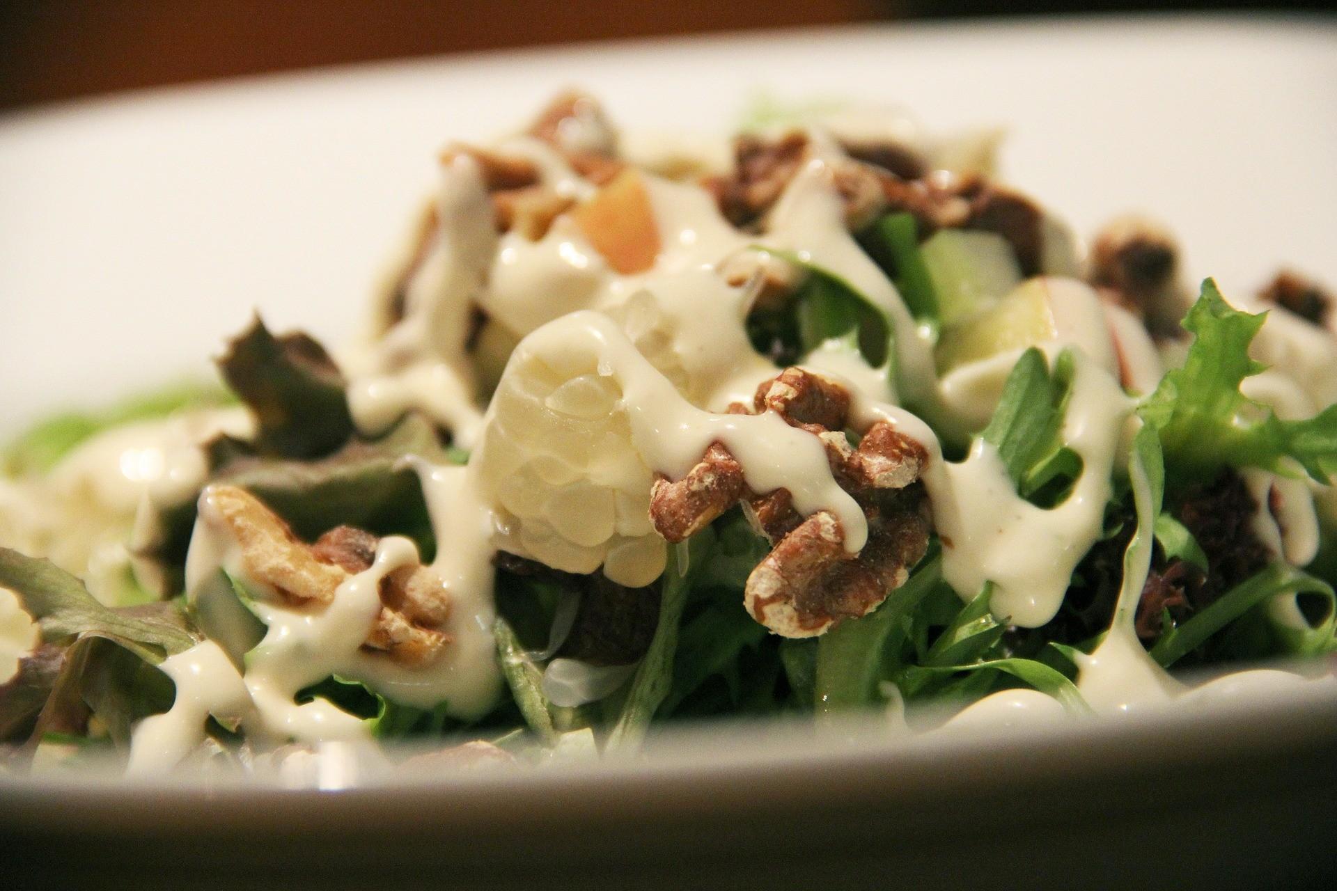 Bild: grüner Salat mit Baumnüssen und weisser Sauce.