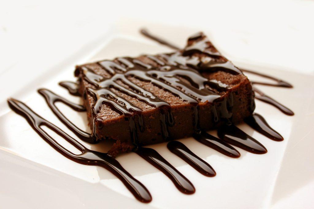 Bild: Vollwert-Brownie auf weissem Teller mit flüssiger Schokoladensauce