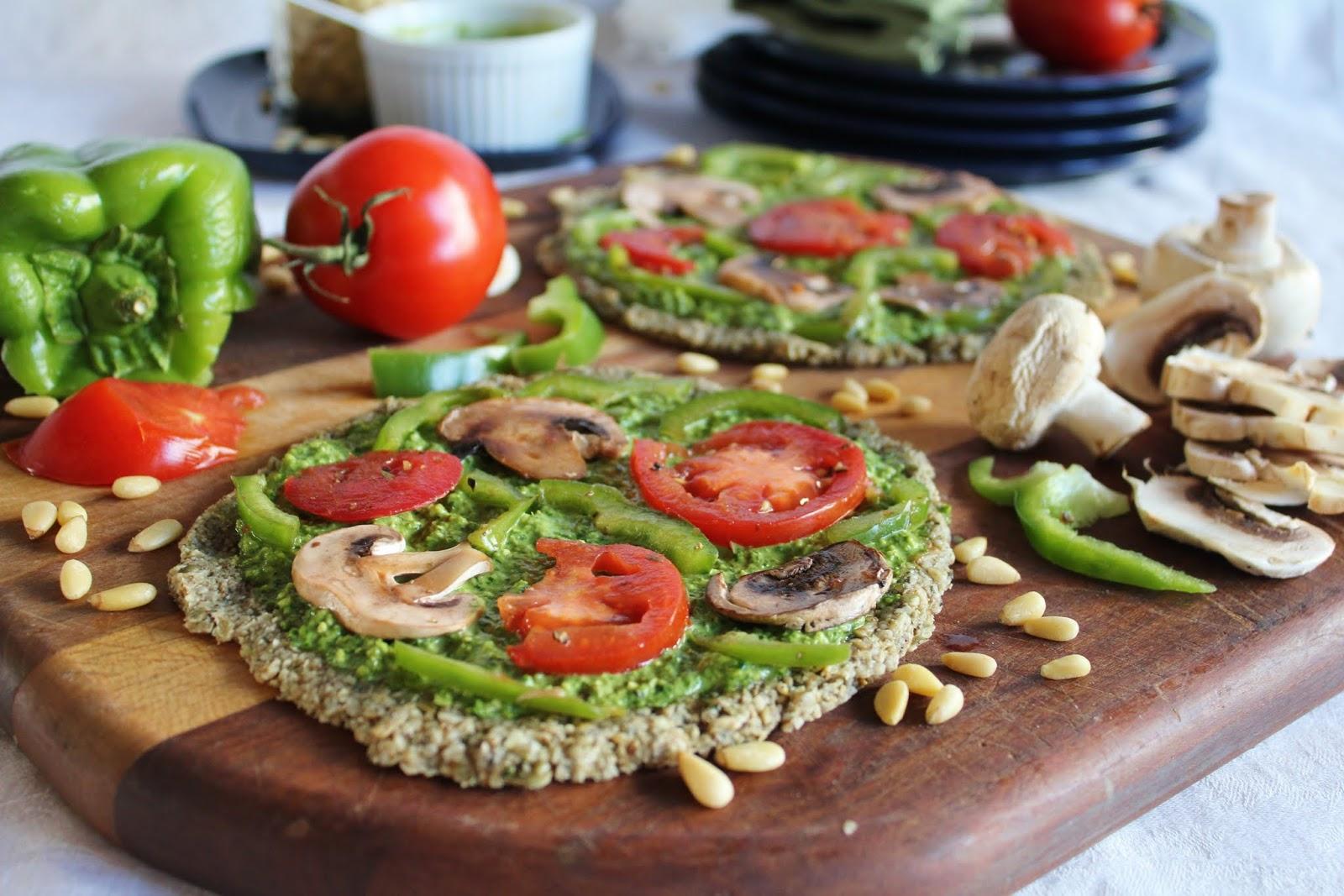 Bild: Rohkostpizza belegt mit Pesto, Tomaten, Champignons und Peperoni.