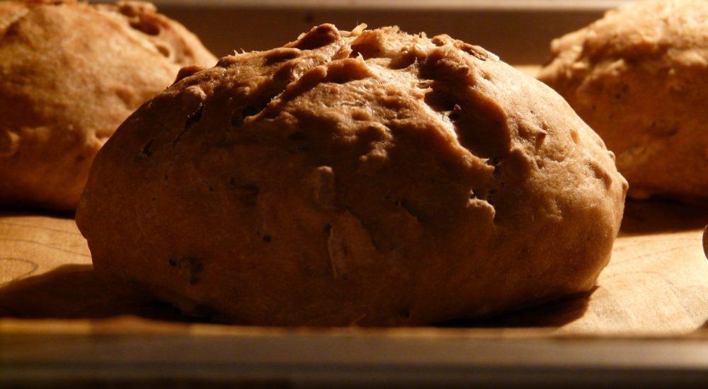 Bild: Brotbackkurs - 3 dunkle Vollkornbrötchen auf Holzunterlage