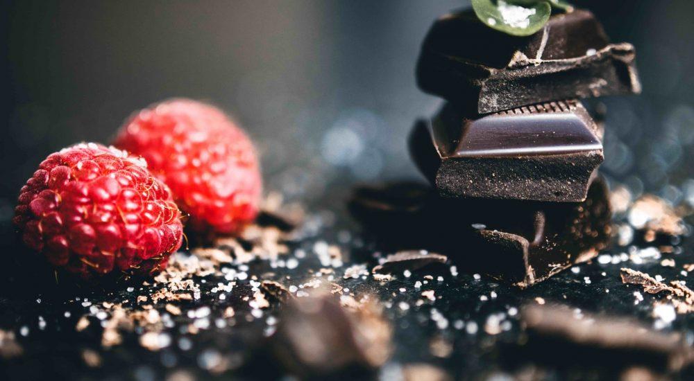 Bild: Schokoladenkurs - 4 Stücken dunkle Vollwertschokolade aufeinander gelegt, mit 2 Himbeeren daneben.