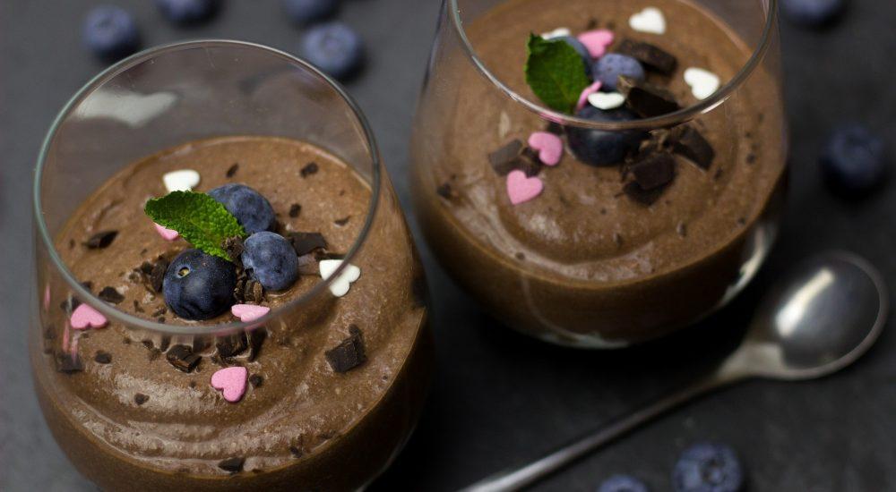 Bild: 2 Gläser mit vollwertigem Schokoladen Glace dekoriert mit chocolate chips und Heidelbeeren auf schwarzem Tisch.