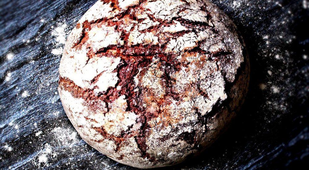 Bild: Brotbackkurs - Ein rundes vollwertiges Vollkornbrot liegt auf einer schwarzen Steinplatte.