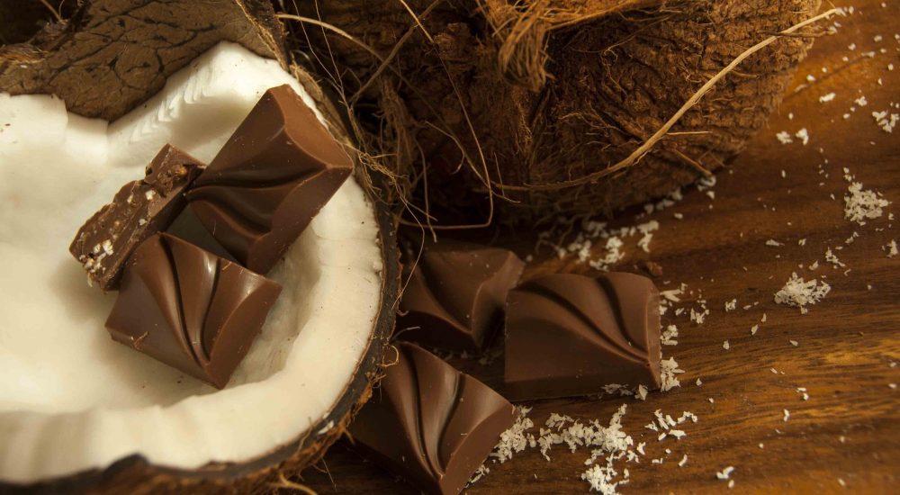 Bild: Schokoladenkurs - 2 Kokospralinen liegen auf dem weissen Fruchtfleisch einer offenen Kokosnuss auf einem braunen Tisch.